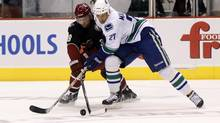 Phoenix Coyotes left wing Brett MacLean and Vancouver Canucks center Manny Malhotra battle for the puck in overtime during an NHL game in Glendale, Arizona, March 8, 2011. (RICK SCUTERI/REUTERS)