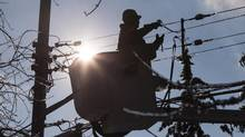 A utility-company worker works on power lines. (CHRIS YOUNG/THE CANADIAN PRESS)