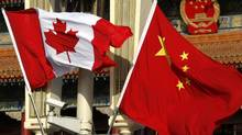 Canadian and Chinese national flags hang from a lamp post in front of the giant portrait of former Chinese Chairman Mao Zedong at Beijing's Tiananmen Square December 2, 2009. (DAVID GRAY/REUTERS)