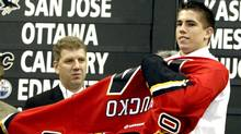Kris Chucko of Burnaby, B.C. puts on the sweater of the Calgary Flames after being picked in the first round of the NHL draft, at the RBC Center In Raleigh, North Carolina, June 26, 2004. (ELLEN OZIER/Reuters)