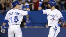 Toronto Blue Jays' Steve Tolleson congratulates teammate Jose Bautista on his three-run homerun during first inning American League baseball action against the Los Angeles Angels in Toronto on Monday, May 12, 2014. (Frank Gunn/THE CANADIAN PRESS)