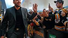 Bruins winger Milan Lucic high-fives fans as the team departs the TD Garden in Boston for Chicago on Tuesday. (Nancy Lane/AP)