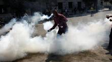 An Egyptian protester throws back a tear gas canister toward riot police, unseen, during clashes outside the U.S. embassy in Cairo, Egypt, Thursday, Sept. 13, 2012. Protesters clash with police near the U.S. Embassy in Cairo for the third day in a row. Police used tear gas to disperse the demonstrators and the two sides pelted each other with rocks. (Nasser Nasser/AP)