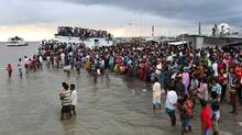 People gather on the banks of the River Padma after a passenger ferry capsized in Munshiganj district, Bangladesh, Monday, Aug. 4, 2014. (A.M. Ahad/AP)