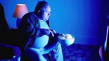 An overweight man eats potato chips while watching television. (PhotoDisc)