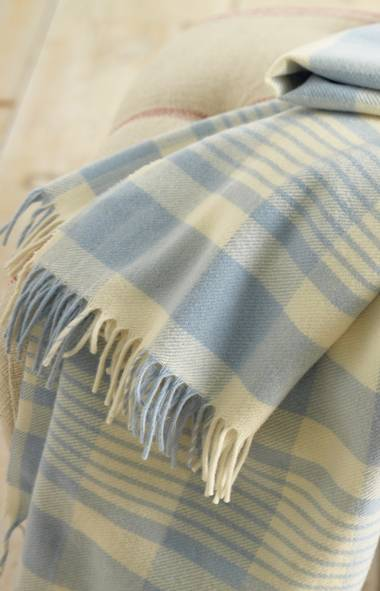 BLANKET STATEMENT: Take time to chill this holiday season under a cozy buffalo-check wool throw, wrapping yourself in either soft blue or silvery charcoal – clever updates on a classic staple. Buffalo check throw, $154 through www.garnethill.com. (Handout)