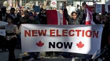 Protesters take the streets in downtown Toronto on March 11, 2012 in response to the widening robo-call election scandal. (Chris Young/Chris Young/Reuters)