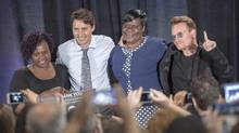 From left, Consolata Opiyo, Justin Trudeau, Patricia Asero Ochieng and Bono pose for photos in Montreal on Saturday after a town hall meeting for the One Campaign on the fight against poverty. (Ryan Remiorz/THE CANADIAN PRESS)
