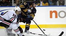 Buffalo Sabres' Nathan Gerbe (42) passes under pressure from Chicago Blackhawks' Patrick Sharp (10) during the first period of an NHL hockey game in Buffalo, N.Y., Friday, Dec. 11, 2009. (AP Photo/ David Duprey) (David Duprey)