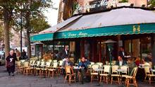 Some customers sit on the terrace of the famous Paris cafe of Deux Magots, at the Saint-Germain-des-Pres Square, 14 November 2001 . (ERIC FEFERBERG/AFP)