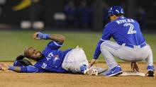 Toronto Blue Jays shortstop Jose Reyes (L) reacts to the pain after hurting his ankle while trying to steal second as third base coach Luis Rivera comes to help in the sixth inning against the Kansas City Royals at their American League baseball game in Kansas City, Missouri April 12, 2013. (DAVE KAUP/REUTERS)