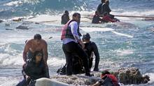 Migrants are rescued by Greek Coast Guard members and locals after a wooden sailboat carrying dozens of immigrants ran aground off the coast of Rhodes. At least three people drowned. (Reuters)