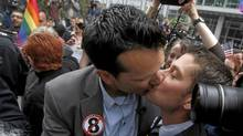 Spencer Jones, left, kisses his husband, Tyler Barrick, outside court in San Franciso Wednesday after a federal judge overturned California's same-sex marriage ban. (Jeff Chiu/The Associated Press)