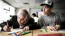 Syrian refugees Nada Alkhamis, 13, and her brother, Abdulrahman, 15, practise writing their names in Surrey, B.C., on Wednesday. (John Lehmann/The Globe and Mail)