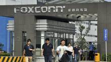 Workers walk out of the entrance to a Foxconn factory in Chengdu, Sichuan province. (STRINGER/CHINA/REUTERS)