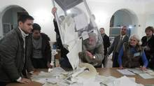 Members of a local electoral commission empty a ballot box at a polling station after voting day in Kiev, on Oct. 28, 2012. (GLEB GARANICH/REUTERS)