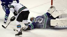 Vancouver Canucks' Roberto Luongo, right, stops San Jose Sharks' Joe Pavelski during the third period of an NHL hockey game in Vancouver, B.C., on Thursday January 20, 2011. (DARRYL DYCK)