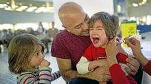 Juan Mosquera holds his son Jasper, 4, as he receives a flu shot with little sister Hazel, 3, looking on at city hall in Toronto, Ont. Jan. 11, 2011. (Kevin Van Paassen/The Globe and Mail/Kevin Van Paassen/The Globe and Mail)