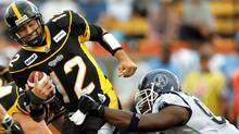 Hamilton Tiger-Cats quarterback Quinton Porter is sacked by Toronto Argonauts defensive end Ronald Flemons (R) during the first half of their CFL football game in Hamilton. (MIKE CASSESE/MIKE CASSESE/REUTERS)