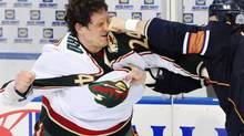 Minnesota Wild left wing Derek Boogaard (24) gets hit by Edmonton Oilers left wing Steve MacIntyre (33) in a fight during first period NHL action in Edmonton on Jan. 30, 2009. A number of pro football and hockey players, who had suffered repeated concussions have had symptoms suggestive of chronic traumatic encephalopathy, or CTE. (Jimmy Jeong/THE CANADIAN PRESS)