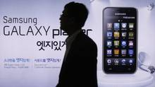 A man walks by an advertisement for Samsung's smartphone Galaxy in Seoul, South Korea, Tuesday, April 19, 2011. Apple Inc. has sued Samsung Electronics Co., saying the South Korean company's Galaxy line of smartphones and tablet computers copy Apple's popular iPad and iPhone. (Ahn Young-joon/AP)