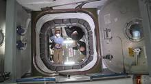 Crew members on the International Space Station open a hatch to begin unloading cargo during their continuing space mission. (Reuters)