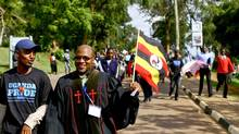 Ugandan anti-gay activist Pastor Martin Ssempa carries a national flag while leading a procession backing the signing of the anti-gay bill into law, in Uganda's capital Kampala March 31, 2014. (© Stringer . / Reuters/REUTERS)