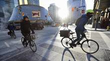 Cyclists on Simcoe St. head north while crossing King St. West on Jan 11 2016. (Fred Lum/The Globe and Mail)