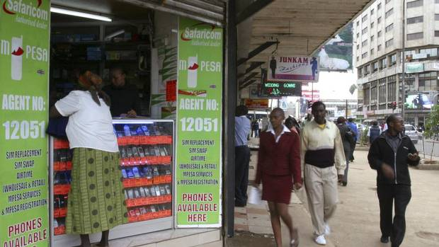 Pedestrians walk past an M-PESA mobile banking shop in downtown Nairobi, Kenya, on May 12, 2009. (NOOR KHAMIS/REUTERS)