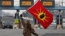 A man waves a flag as Aboriginal protesters and supporters in the Idle No More movement block the Blue Water Bridge border crossing to the United States in Sarnia, Ont. on Saturday, January 5, 2013. (Dave Chidley/THE CANADIAN PRESS)