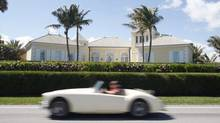 A car makes its way past Conrad Black's home in West Palm Beach, Fla. (Adrian Wyld/The Canadian Press)