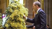 Australian Prime Minister Tony Abbott and his wife Margaret (obscured) place wattle blossoms on a wreath as they attend a national memorial service for the victims of Malaysia Airlines flight MH17 at St Patrick's Cathedral in Melbourne August 7, 2014. (MARK DADSWELL/REUTERS)