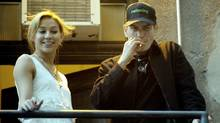 Charlie Sheen smokes a cigarette with, Natalie Kenly, one of his goddesses, on a fire escape before his show at Massey Hall in Toronto. (J.P. Moczulski for The Globe and Mail)