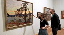 """Exhibition officer Amy Concannon (L) and designer Eric Pearson view Canadian artist Tom Thomson's 1917 oil painting """"The Jack Pine"""" at the Dulwich Picture Gallery in London on Oct. 14, 2011. The gallery is hosting """"Painting Canada: Tom Thomson and the Group of Seven"""" from Oct. 19, 2011 to Jan. 8, 2012. (Chris Helgren/Reuters/Chris Helgren/Reuters)"""
