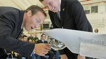 National Defence Minster Peter MacKay Public Works Minister Christian Paradis, look over a model of a Scan Eagle UAV in St. Hubert, Que., on July 7, 2008. (Graham Hughes/THE CANADIAN PRESS)