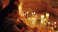 Children light candles inside the ornate sarcophagus of St. Nicholas, inside the church of St. Nicholas in the town of Demre, Turkey, on Dec. 6, 2000. An Italian merchant broke his sarcophagus and took his relics to Bari, Italy in 1087. (SELCAN HACAOGLU/Associated Press)