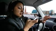 New driver Brandi Eadie, 16, reads a text message as she drives through a rubber-cone course in Seattle in January to demonstrate the dangers of phone use while driving. Eadie, who volunteered for the Driven to Distraction Task Force of Washington State event because she thought she could show organizers that she could safely drive and text at the same time, knocked down multiple cones meant to simulate where pedestrians or other objects could be. (Elaine Thompson/AP Photo)