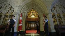 Guards stand outside the Senate chamber on Parliament Hill in Ottawa on May 9, 2013. (CHRIS WATTIE/REUTERS)