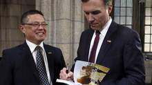 Canada's Finance Minister Bill Morneau signs a copy of the budget for Raymond Louie, president of the Federation of Canadian Municipalities, after delivering the budget on Parliament Hill in Ottawa March 22, 2016. REUTERS/Patrick Doyle (PATRICK DOYLE/REUTERS)