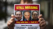 Sam Noh, son of Shin Noh, who went missing from Coquitlam in September, holds missing-person posters of his father in Port Moody, B.C., on Dec. 11, 2013. (Rafal Gerszak for The Globe and Mail)