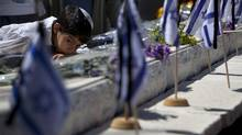 An Israeli child leans on the grave of a relative during a ceremony marking Memorial Day on the Mount of Olives overlooking Jerusalem's Old City on Monday, April 15, 2013. Israelis paused to honor fallen soldiers and victims of terrorism. (Sebastian Scheiner/Associated Press)