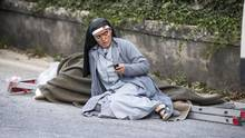 A nun checks her mobile phone as she lies near a victim laid on a ladder following an earthquake in Amatrice Italy, Wednesday, Aug. 24, 2016. (Massimo Percossi/AP)