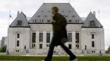 A woman walks past the Supreme Court of Canada in Ottawa on June 20, 2008. (Tom Hanson/The Canadian Press)