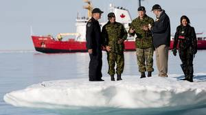 Prime Minister Stephen Harper stands on an iceberg as he talks with Chief of the Defence Staff General Walter Natynczyk during Operation Nanook in Resolute, Nunavut, on Aug. 25, 2010.