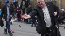 Toronto Mayor Rob Ford tosses chocolate eggs to the crowd as he walks in the Beaches Easter Parade in Toronto. (Chris Young for The Globe and Mail)