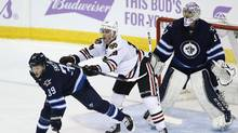 Chicago Blackhawks' Jonathan Toews (19) clears Winnipeg Jets' Toby Enstrom (39) as he attempts to screen Jets goaltender Connor Hellebuyck (37) during third period NHL action in Winnipeg on Tuesday, November 15, 2016. (JOHN WOODS/THE CANADIAN PRESS)