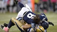 Winnipeg Blue Bombers' Max Hall is sacked by Toronto Argonauts' Marcus Ball during second quarter CFL action in Toronto on Thursday Oct. 24, 2013. (FRANK GUNN/THE CANADIAN PRESS)