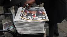 A passerby picks up a copy of the London Evening Standard newspaper, featuring a picture of U.S. President-elect Donald Trump on its front page, in the square mile financial district of London on Wednesday, Nov. 9. (Chris Ratcliffe/Bloomberg)