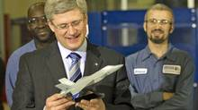 Prime Minister Stephen Harper looks at a model of a fighter-jet during a visit to the Heroux-Devtek plant near Montreal on Jan. 14, 2011. (Ryan Remiorz/The Canadian Press)