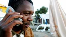 A township resident chats on his mobile phone in Hout Bay near Cape Town in this 2006 file photo. (MIKE HUTCHINGS/REUTERS/Mike Hutchings)